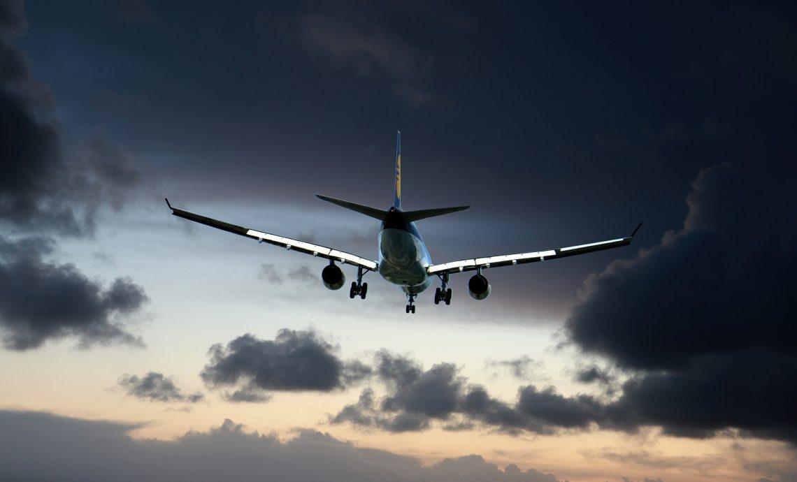 Flygplan flyger mot gråa moln